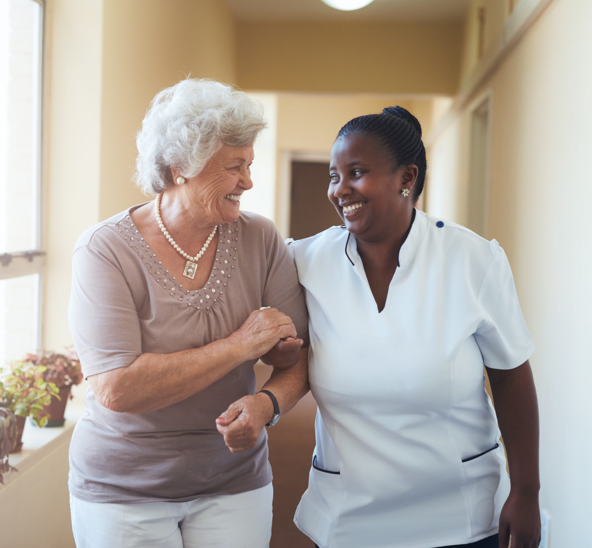 A nurse and patient walking together and smiling